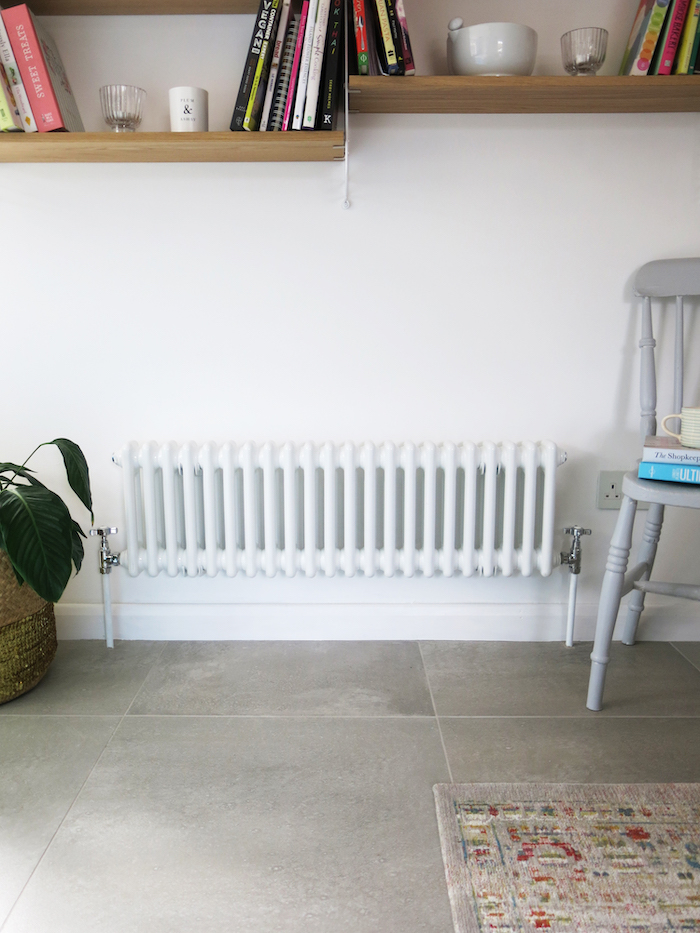 Classic vintage style radiator in white grey floor blue kitchen