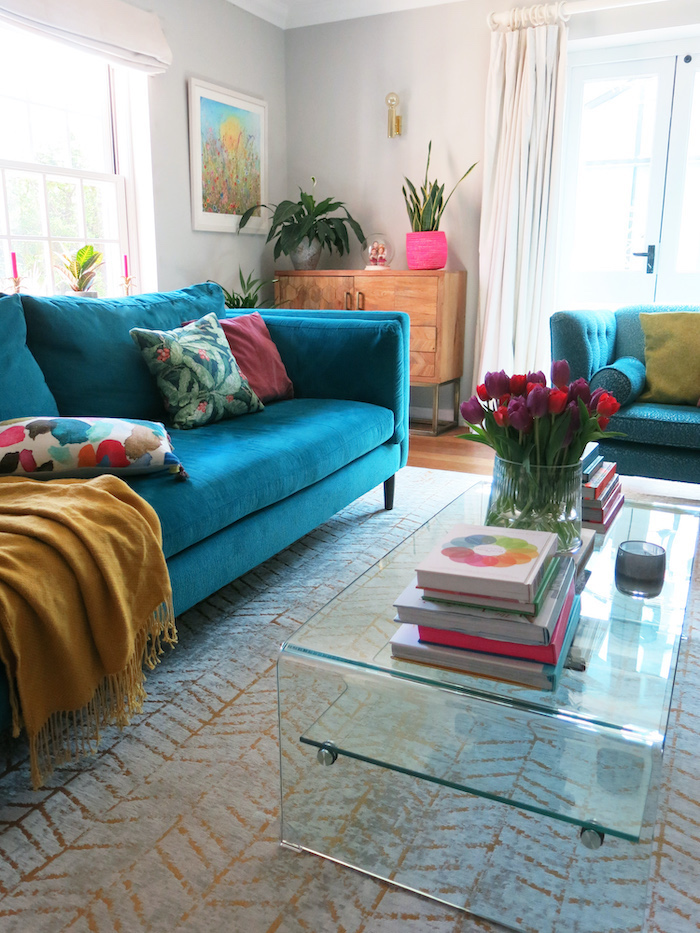 teal sofa in living room with grey walls and gold rug